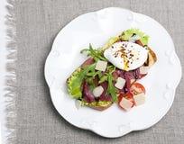 Bocadillo con los huevos escalfados y el jamon Foto de archivo