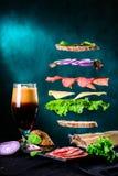 Bocadillo con los ingredientes que caen en el aire y la cerveza oscura en a Foto de archivo libre de regalías