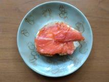 Bocadillo con los pedazos de pescados rojos en el pan blanco manchado con aceite, un desayuno, bocado foto de archivo libre de regalías