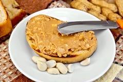 Bocadillo con mantequilla y el cuchillo de cacahuete en servilleta Fotos de archivo libres de regalías