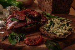 bocadillo con pesto, los tomates secados al sol, la albahaca, el arugula y la carne de vaca ahumada Foto de archivo
