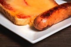 Bocadillo con queso derretido y el primer frito de la salchicha contra t foto de archivo libre de regalías