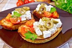 Bocadillo con queso Feta y aceitunas en mantel Fotos de archivo