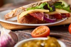 Bocadillo con tocino, queso, ajo, pimienta del jalapeno e hierbas en una placa fotografía de archivo libre de regalías