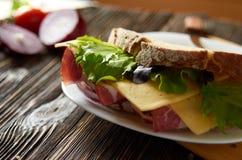 Bocadillo con tocino, queso e hierbas en una placa foto de archivo
