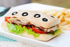Bocadillo de Ciabatta con carne de vaca, los tomates, el queso y la lechuga asados a la parrilla con el fondo del verano de las p Foto de archivo