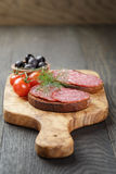 Bocadillo de Rye con el salami y los tomates en la madera Fotos de archivo