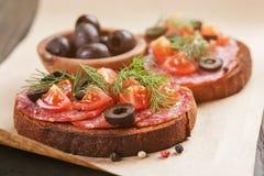 Bocadillo de Rye con el salami y los tomates en la madera Imágenes de archivo libres de regalías