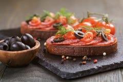 Bocadillo de Rye con el salami y los tomates en la madera Imagen de archivo
