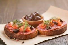 Bocadillo de Rye con el salami y los tomates en la madera Imagen de archivo libre de regalías