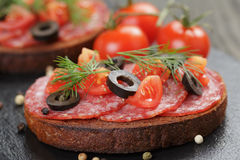 Bocadillo de Rye con el salami y los tomates en la madera Imagenes de archivo