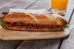 Bocadillo del Baguette con el salami y las hierbas en una superficie de madera imagen de archivo