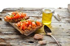 Bocadillo del bruschetta del verano con los tomates, el aceite de oliva, la albahaca y el orégano Foto de archivo libre de regalías