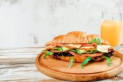 Bocadillo del cruasán con arugula del pavo, del queso y de la ensalada en la tabla de madera blanca con el jugo Imágenes de archivo libres de regalías
