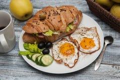 Bocadillo del cruasán con Fried Eggs, pepinos y aceitunas, frutas y verduras frescas y taza de café en la placa blanca sobre r gr fotos de archivo