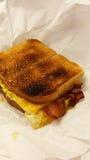 Bocadillo del desayuno del queso del tocino del huevo Foto de archivo libre de regalías