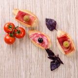 Bocadillo del pan blanco con el salami, el jamón, el queso y la aceituna negra Fotos de archivo