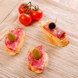 Bocadillo del pan blanco con el salami, el jamón, el queso y la aceituna negra Imagen de archivo libre de regalías