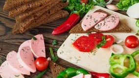 Bocadillo del pan de centeno con la salchicha hervida en un fondo de madera rústico Fotos de archivo libres de regalías
