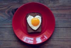 Bocadillo del pan de centeno con los huevos revueltos bajo la forma de corazón Imágenes de archivo libres de regalías