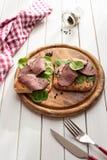 Bocadillo del rosbif con la ensalada y la pimienta en la placa de madera rústica Fotografía de archivo libre de regalías