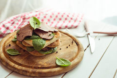 Bocadillo del rosbif con la ensalada y la pimienta en la placa de madera rústica el tono Fotografía de archivo