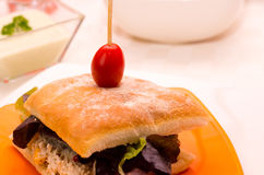Bocadillo delicioso del ciabatta con el top ensartado del tomate de cereza, sentándose en la placa blanca, concepto de abastecimi Fotografía de archivo libre de regalías