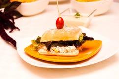Bocadillo delicioso del ciabatta con el top ensartado del tomate de cereza, sentándose en la placa blanca, concepto de abastecimi Imagen de archivo libre de regalías