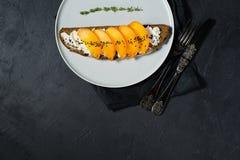 Bocadillo equilibrado sano de la comida con el caqui y queso suave en fondo negro fotos de archivo libres de regalías