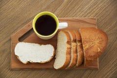 Bocadillo fresco con queso en un tablero de madera con el café para el desayuno Foto de archivo