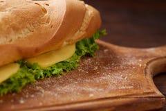 Bocadillo fresco y sabroso con queso y verduras en tabla de cortar sobre el fondo de madera, foco selectivo Fotos de archivo