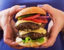 Bocadillo grande - hamburguesa de la hamburguesa con carne de vaca, queso, el tomate y la salsa de tártaro Foto de archivo libre de regalías
