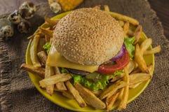 Bocadillo grande - hamburguesa de la hamburguesa con la carne de vaca, queso, tomate En un fondo rústico de madera Primer Foto de archivo libre de regalías