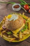 Bocadillo grande - hamburguesa de la hamburguesa con la carne de vaca, queso, tomate En un fondo rústico de madera Visión superio Fotos de archivo
