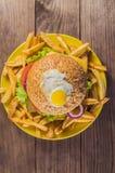 Bocadillo grande - hamburguesa de la hamburguesa con la carne de vaca, queso, tomate En un fondo rústico de madera Visión superio Fotos de archivo libres de regalías