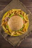 Bocadillo grande - hamburguesa de la hamburguesa con la carne de vaca, queso, tomate En un fondo rústico de madera Visión superio Imágenes de archivo libres de regalías