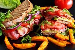 Bocadillo hecho en casa fresco de BLT en el pan asado a la parrilla con tocino, lechuga, el tomate de la carne de vaca, las cebol Fotos de archivo