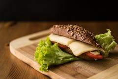 Bocadillo ligero con queso, el tomate y verdes Imagen de archivo libre de regalías