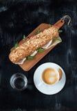 Bocadillo (prosciutto, arugula), café y agua foto de archivo