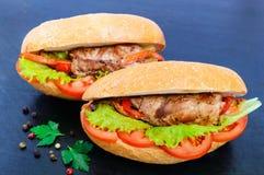 Bocadillo: Rollos de carne con las verduras en un bollo con el tomate Imágenes de archivo libres de regalías