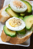 Bocadillo sano del desayuno con el aguacate y los huevos hervidos Imagenes de archivo