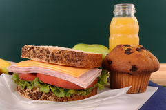 Bocadillo, torta y bebida del almuerzo escolar en el escritorio de la sala de clase con la pizarra Imagen de archivo libre de regalías