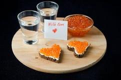 Bocadillo tres con el caviar rojo bajo la forma de corazón, vodka imagenes de archivo