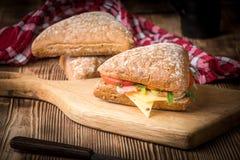 Bocadillo triangular con queso, el jam?n y el tomate imagen de archivo