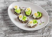 Bocadillos abiertos con el queso cremoso, los huevos de codornices y el apio Bocado sano delicioso de Pascua Fotografía de archivo libre de regalías