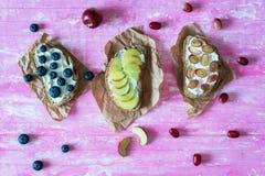 Bocadillos abiertos sanos con las frutas, los ar?ndanos de las uvas del melocot?n y el queso suave en fondo de madera rosado imágenes de archivo libres de regalías