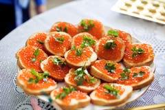Bocadillos con el caviar de color salmón Fotos de archivo libres de regalías