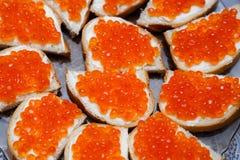 Bocadillos con el caviar de la mantequilla y de los salmones rojos Imagen de archivo libre de regalías