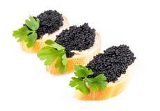 Bocadillos con el caviar negro aislado en blanco Foto de archivo libre de regalías