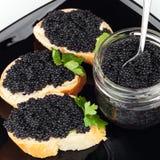 Bocadillos con el caviar negro en la placa Imagen de archivo